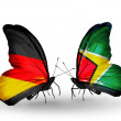 Two butterflies with flags on wings as symbol of relations Germany and Guyana — Stock Photo #32731775