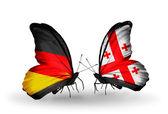 Två fjärilar med flaggor på vingarna som symbol för förbindelserna mellan tyskland och georgien — Stockfoto