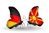 Two butterflies with flags on wings as symbol of relations Germany and Macedonia — Stock Photo