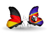 Two butterflies with flags on wings as symbol of relations Germany and Switzerland — Stock Photo