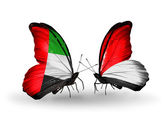 Two butterflies with flags on wings as symbol of relations UAE and Monaco or Indonesia — Stok fotoğraf