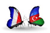 Två fjärilar med flaggor på vingarna som symbol för förbindelserna mellan frankrike och azerbajdzjan — Stockfoto
