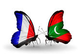 Two butterflies with flags on wings as symbol of relations France and Maldives — 图库照片