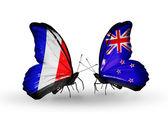 Två fjärilar med flaggor på vingarna som symbol för förbindelserna mellan frankrike och nya zeeland — Stockfoto