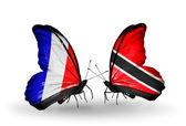 Två fjärilar med flaggor på vingarna som symbol för förbindelserna mellan frankrike och trinidad och tobago — Stockfoto