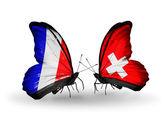 Två fjärilar med flaggor på vingarna som symbol för förbindelserna mellan frankrike och schweiz — Stockfoto