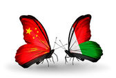 Two butterflies with flags on wings as symbol of relations China and Madagascar — Stock Photo