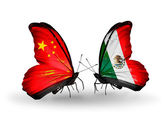 Two butterflies with flags on wings as symbol of relations China and Mexico — Stock Photo
