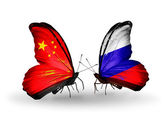 Two butterflies with flags on wings as symbol of relations China and Russia — Stockfoto