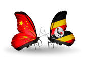 Two butterflies with flags on wings as symbol of relations China and Uganda — Stock Photo