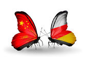 Two butterflies with flags on wings as symbol of relations China and South Ossetia — Stock Photo