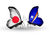 Two butterflies with flags on wings as symbol of relations Japan and Marshall islands — Stock Photo