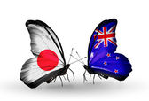 Two butterflies with flags on wings as symbol of relations Japan and New Zealand — Stock Photo
