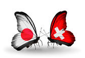 Two butterflies with flags on wings as symbol of relations Japan and Switzerland — Stock Photo