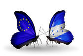 Two butterflies with flags on wings as symbol of relations EU and Honduras — Stock Photo