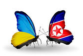 Two butterflies with flags on wings as symbol of relations Ukraine and North Korea — Stock Photo