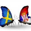 Stock Photo: Two butterflies with flags on wings as symbol of relations Sweden and Serbia