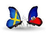 Dva motýli s příznaky na křídlech jako symbol vztahů, švédska a na haiti — Stock fotografie
