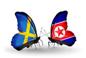 Two butterflies with flags on wings as symbol of relations Sweden and North Korea — Stock Photo