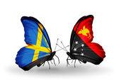 две бабочки с флагами на крыльях как символ отношения швеции и папуа — новой гвинеи — Стоковое фото