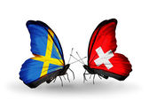 Two butterflies with flags on wings as symbol of relations Sweden and Switzerland — Stock Photo