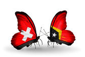 Two butterflies with flags of Switzerland and East Timor on wings — Stock Photo