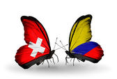 Two butterflies with flags of Switzerland and Columbia on wings — Stock Photo