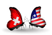 Two butterflies with flags of Switzerland and Liberia on wings — Stock Photo