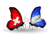 Two butterflies with flags of Switzerland and Nicaragua on wings — Stok fotoğraf