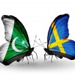 Stock Photo: Two butterflies with flags of Pakistand Sweden on wings