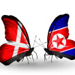 Stock Photo: Two butterflies with flags of Denmark and North Koreon wings