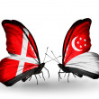 Stock Photo: Two butterflies with flags of Denmark and Singapore on wings