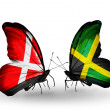 Stock Photo: Two butterflies with flags of Denmark and Jamaicon wings
