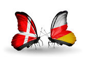 Two butterflies with flags of Denmark and South Ossetia on wings — Stock Photo