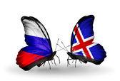 Twee vlinders met vlaggen van Rusland en IJsland op vleugels — Stockfoto