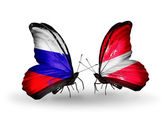 Two butterflies with flags of Russia and Latvia on wings — Stock Photo