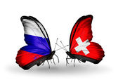 Two butterflies with flags of Russia and Switzerland on wings — Stock Photo