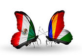 Zwei schmetterlinge mit flaggen der mexiko und auf den seychellen auf flügeln — Stockfoto