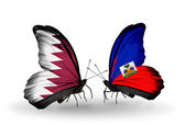 Vlinders met qatar en haïti vlaggen op vleugels — Stockfoto