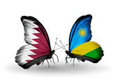 Butterflies with Qatar and Rwanda flags on wings — Stock Photo