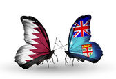 Butterflies with Qatar and Fiji flags on wings — Stock Photo