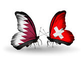 Butterflies with Qatar and Switzerland flags on wings — Stock Photo