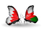 Butterflies with Bahrain and Oman flags on wings — Stock Photo