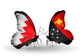 Mariposas con banderas de Bahrein y papua nueva guinea en alas — Foto de Stock