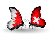 Butterflies with Bahrain and Switzerland flags on wings — Stock Photo