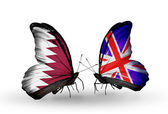 Butterflies with Qatar and UK flags on wings — Stock Photo