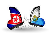 Butterflies with North Korea and San Marino flags on wings — Stock Photo