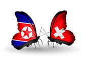 Butterflies with North Korea and Switzerland flags on wings — Stock Photo