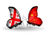 Butterflies with Georgia and China islands flags on wings — Stock Photo