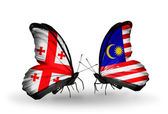 Butterflies with Georgia and Malaysia islands flags on wings — Stock Photo